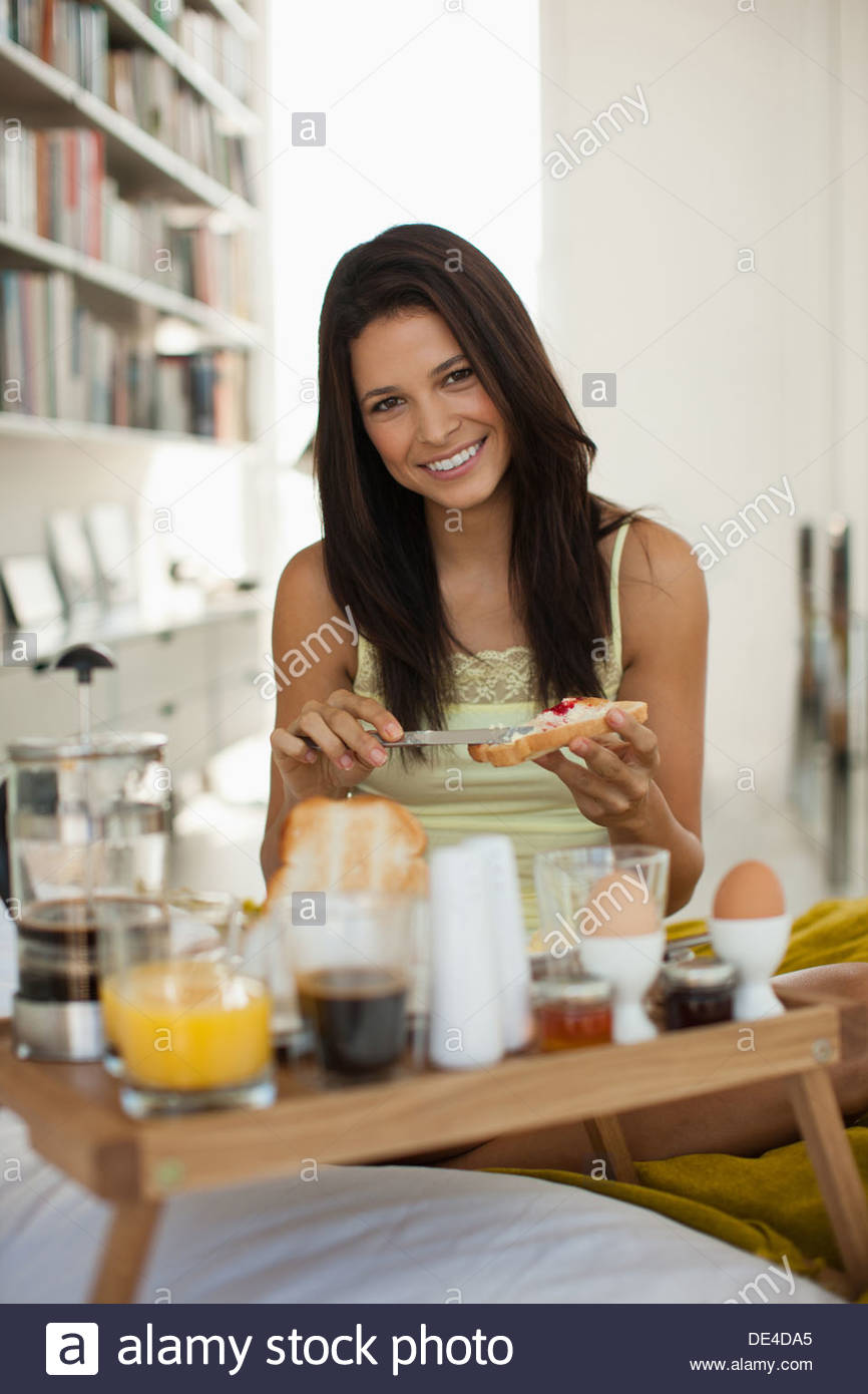 Smiling women having breakfast in bed - Stock Image