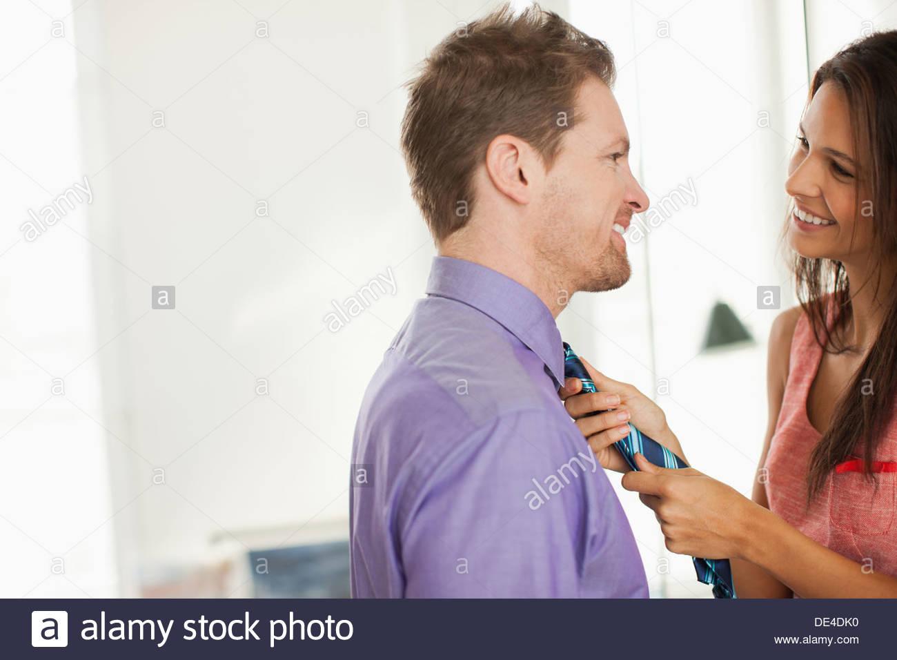 Woman tying husbandÂ's necktie for him - Stock Image
