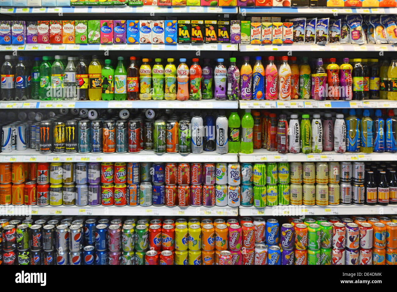 Possible tax on soft drink cans & bottles with some sugary high sugar content & co2 fizzy drinks on shelving inside convenience shop London England UK - Stock Image
