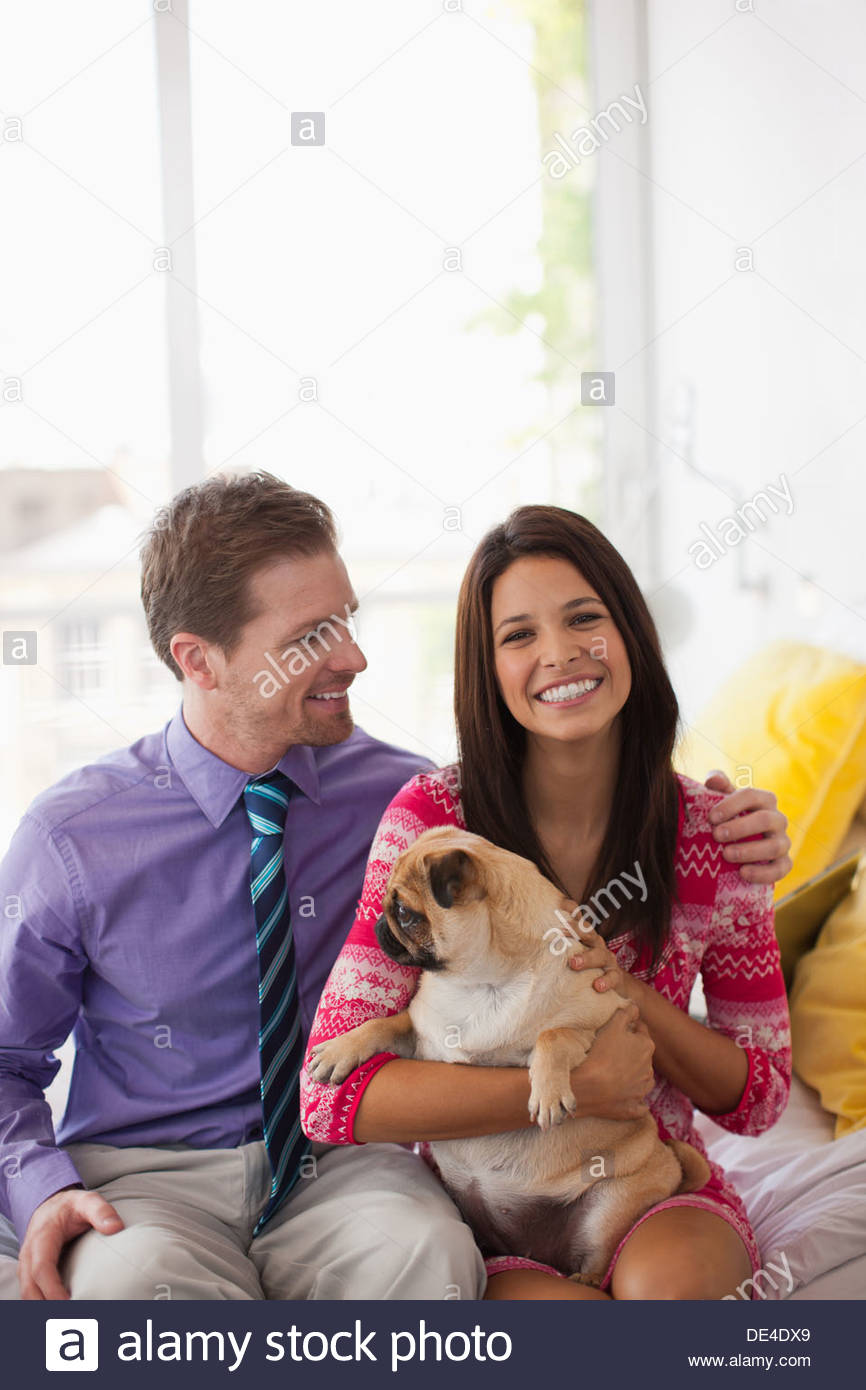 Smiling couple holding cute, small dog - Stock Image