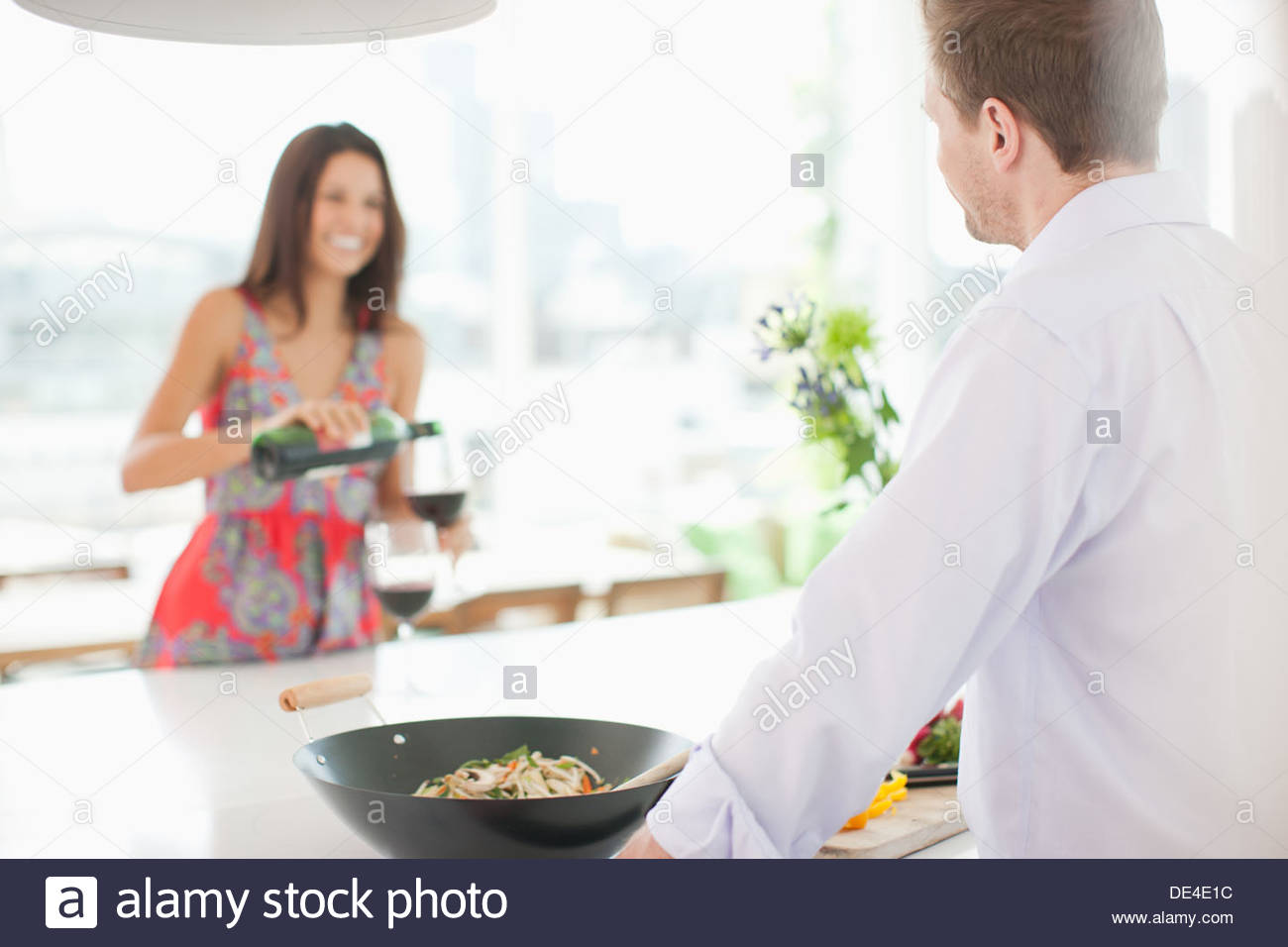 Couple toasting in kitchen with red wine - Stock Image