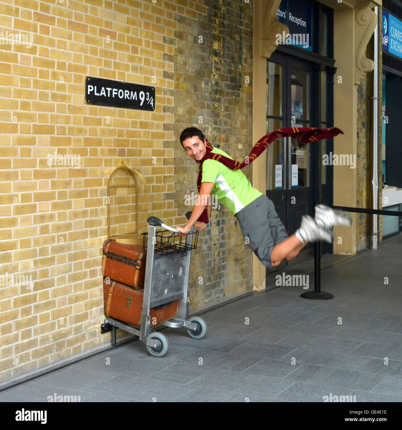 Harry Potter fan recreates pushing a trolley towards platform nine and three quarters from the film Kings Cross railway station London England UK - Stock Image