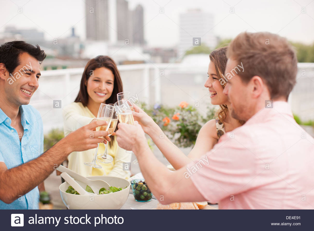 Laughing couples toasting with Champagne outdoors - Stock Image