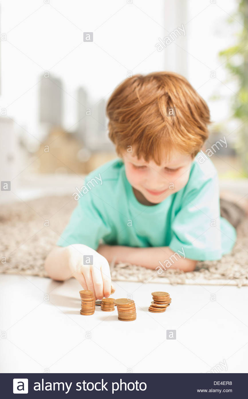 Serious boy stacking pennies on floor - Stock Image