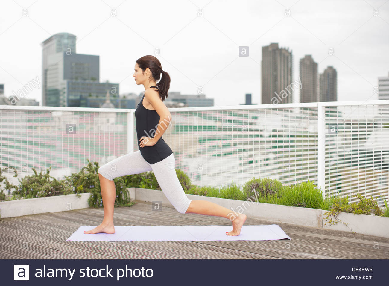 Woman practicing yoga on rooftop deck - Stock Image