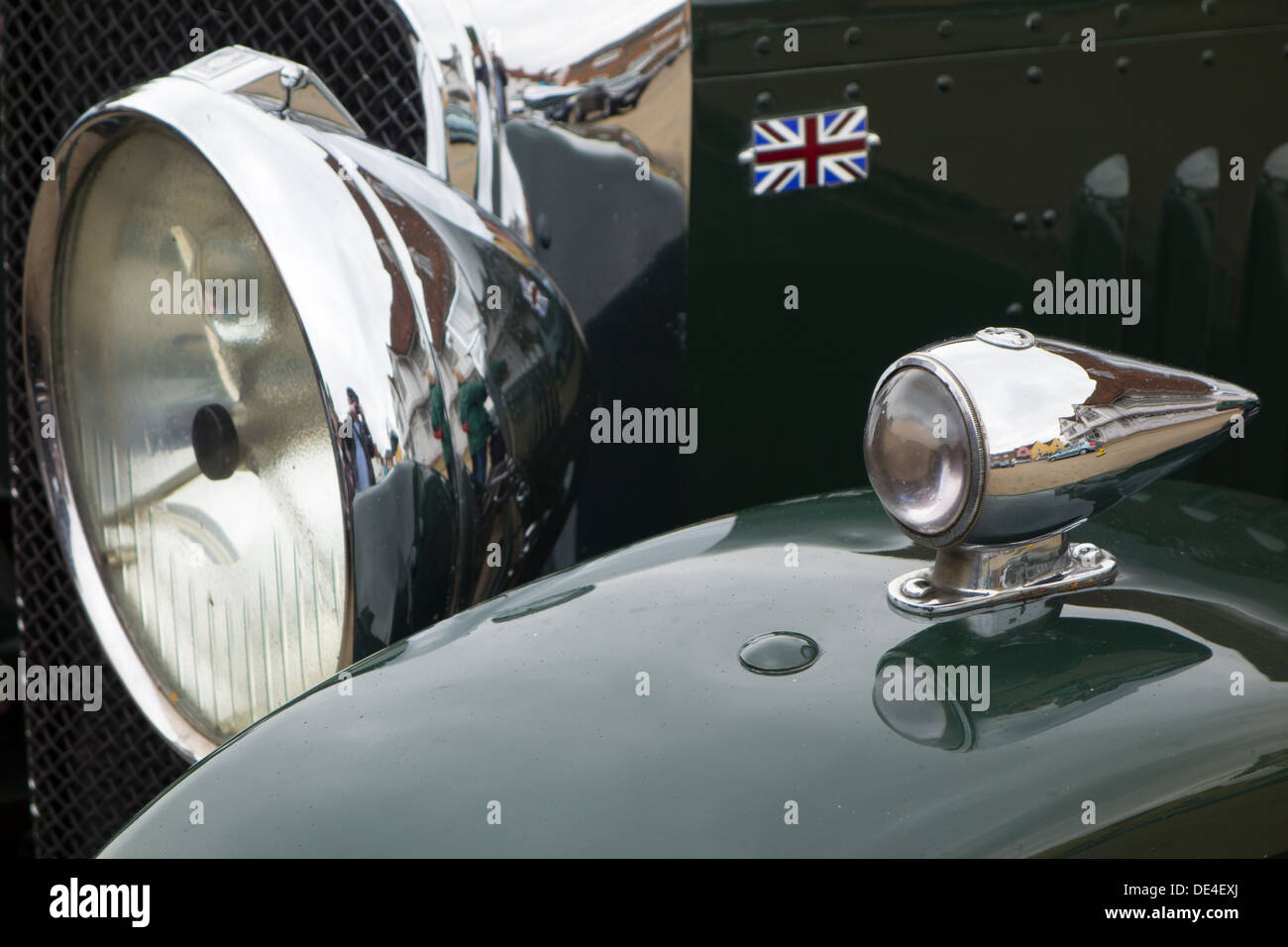 The chrome headlight (headlamps) on the front of a classic British touring car. - Stock Image