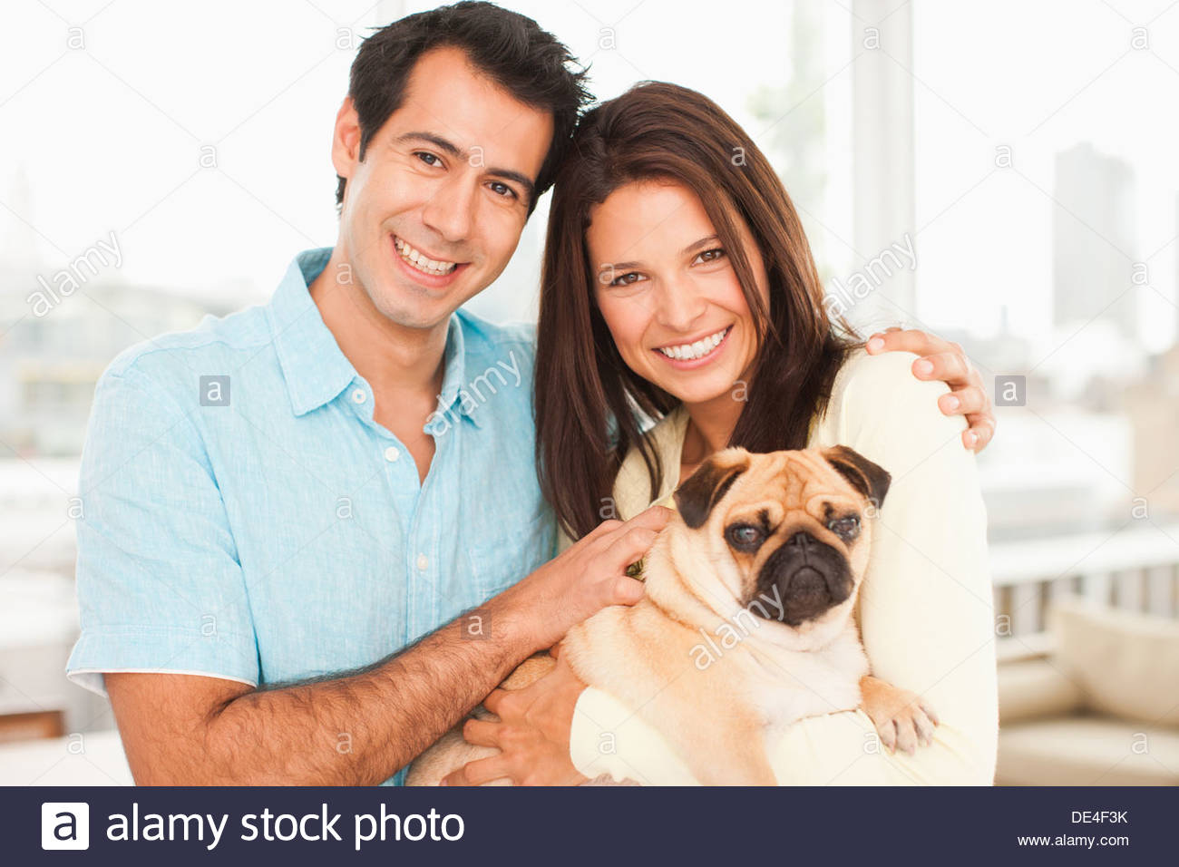 Smiling couple with pug - Stock Image