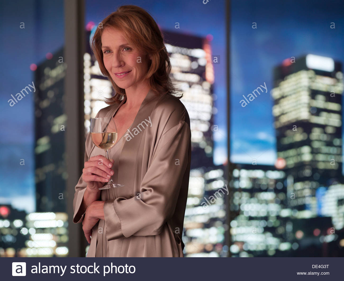 Woman in nightgown drinking white wine at night - Stock Image