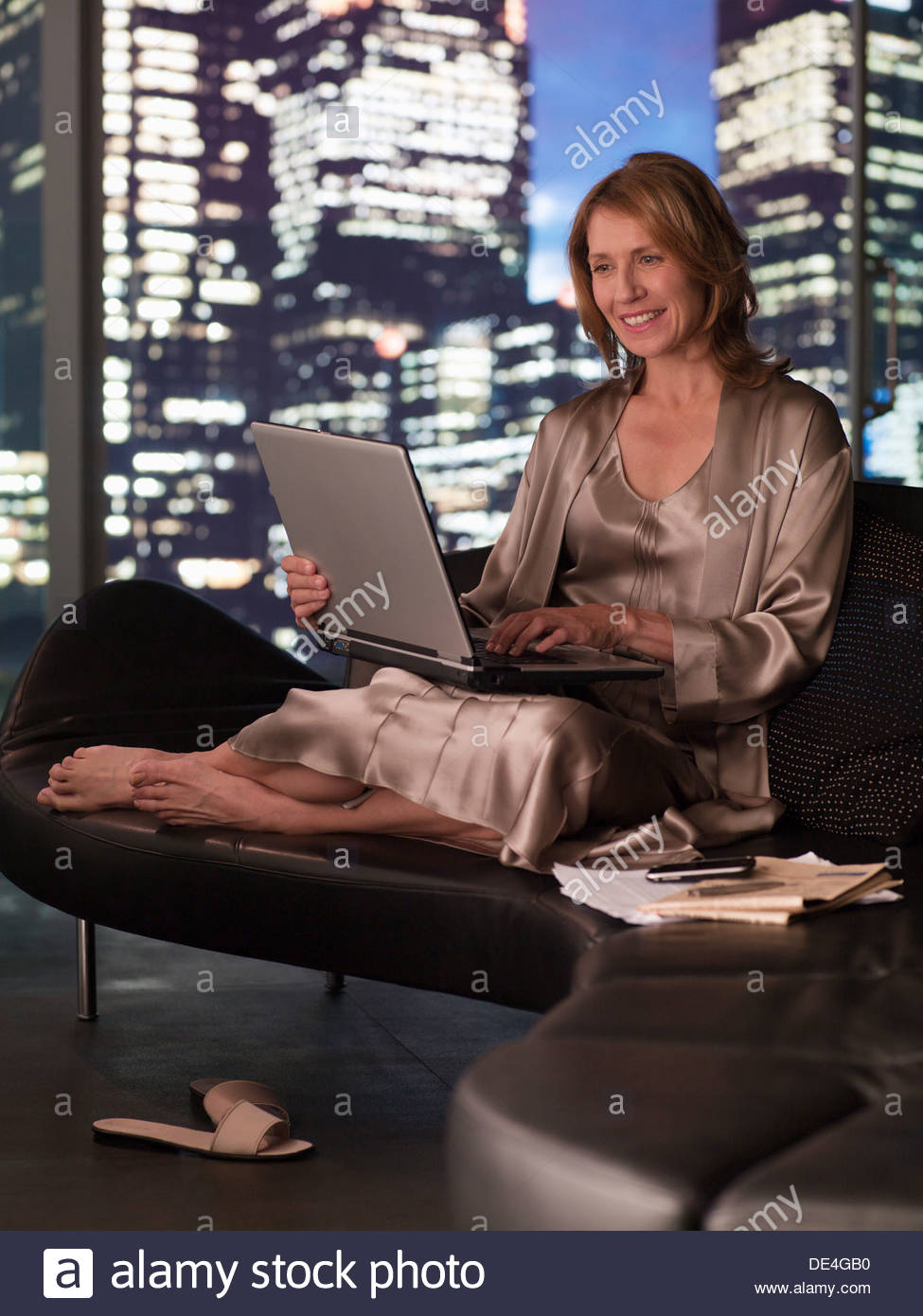 Woman in nightgown using laptop at night - Stock Image