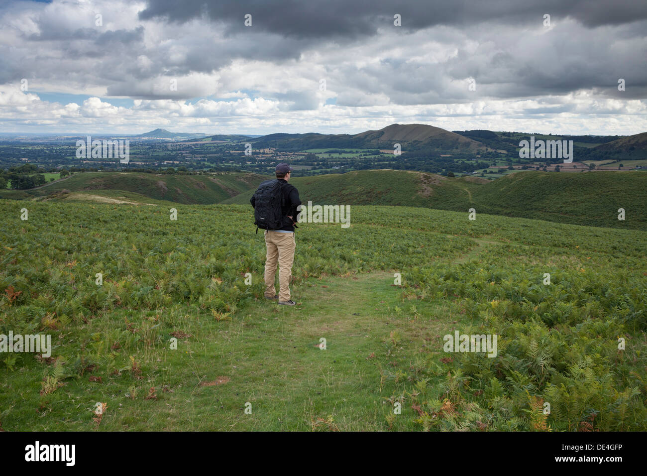 A male walker looking at the Shropshire hills of The Lawley and The Wrekin from The Long Mynd - Stock Image