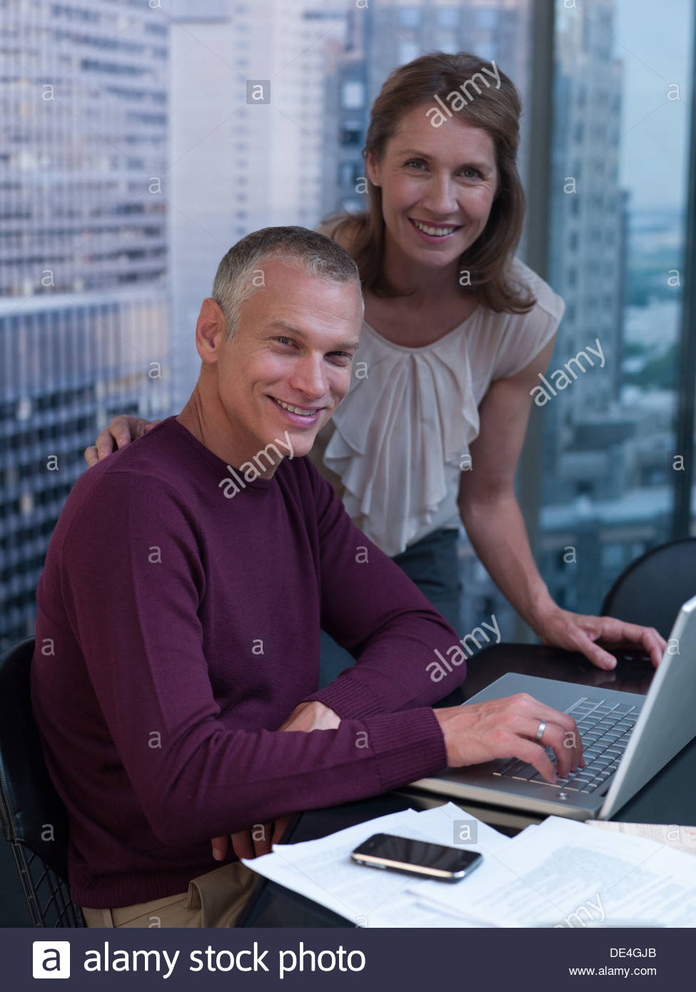 Couple working on computer with cityscape in background - Stock Image