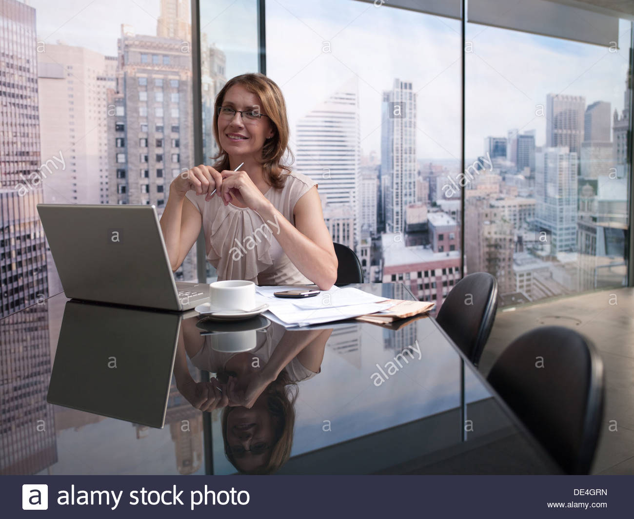 Woman working on computer with cityscape in background - Stock Image
