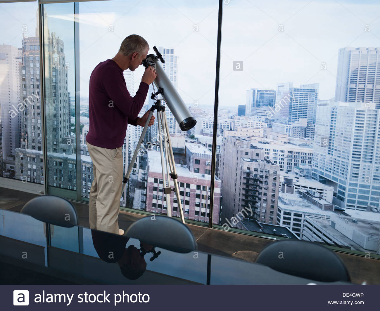 Man using telescope to look at city buildings - Stock Image