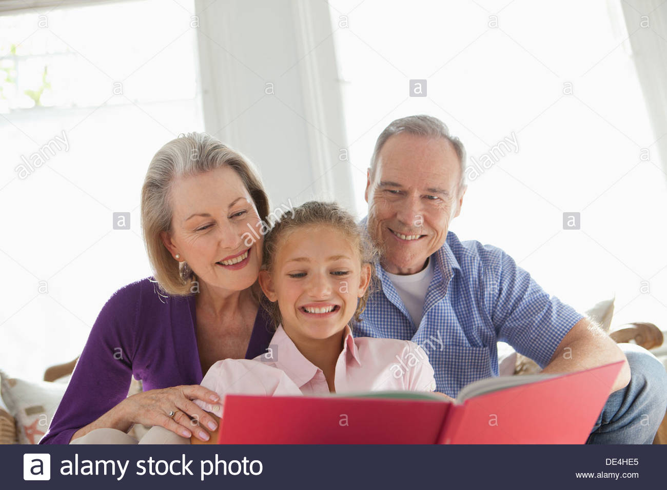 Smiling grandparents and granddaughter reading book - Stock Image