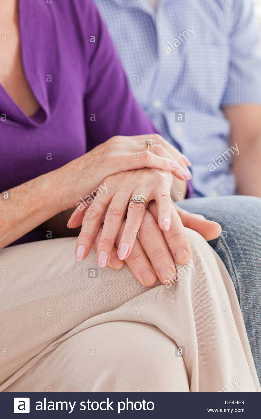 Close up of senior couple touching hands - Stock Image