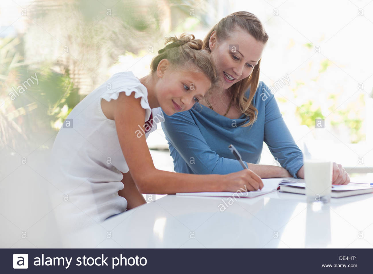 Mother and daughter working on homework together - Stock Image