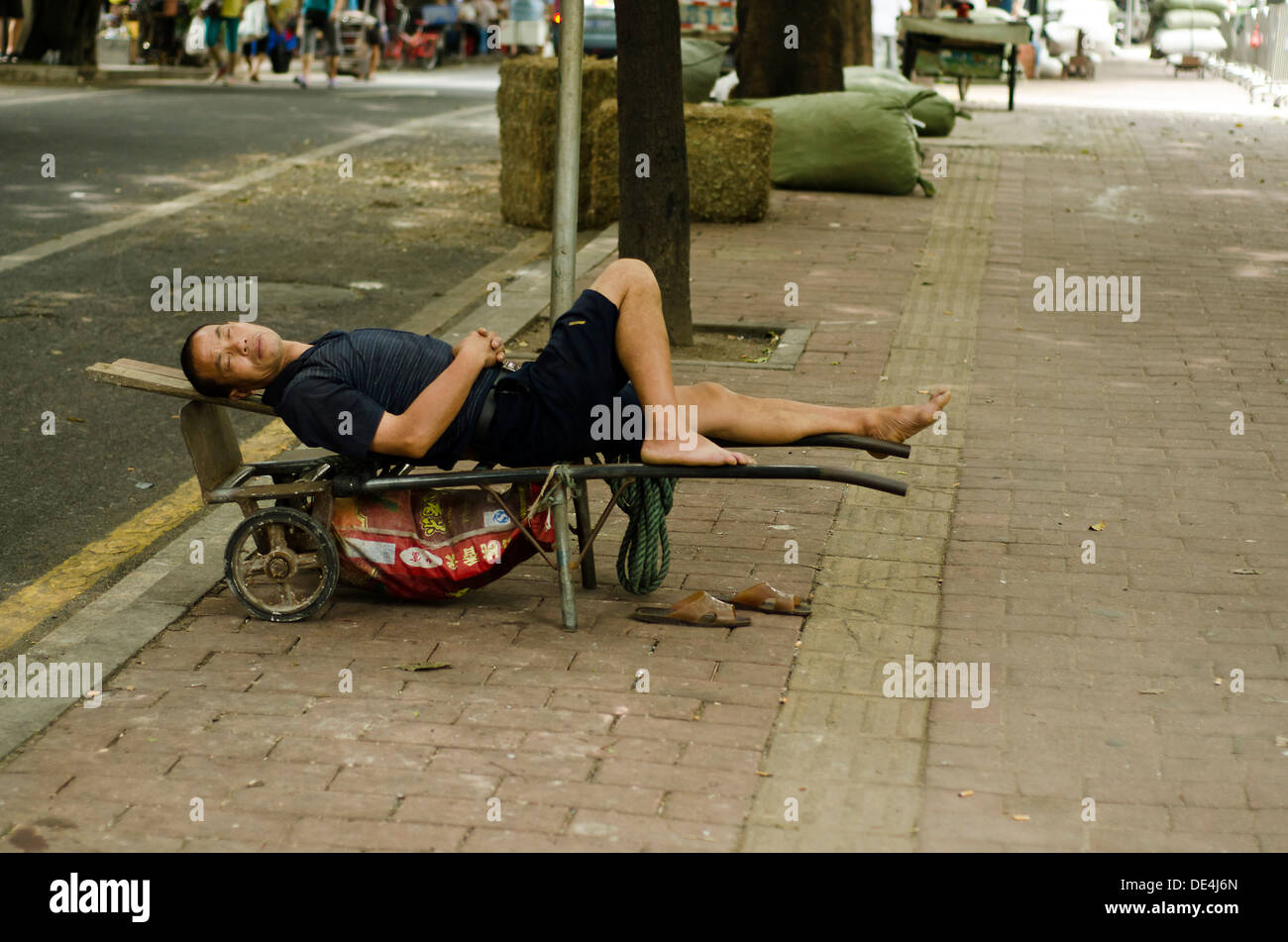 Chinese cart puller sleeps on the side of the road during lunch break , Guangzhou , China - Stock Image
