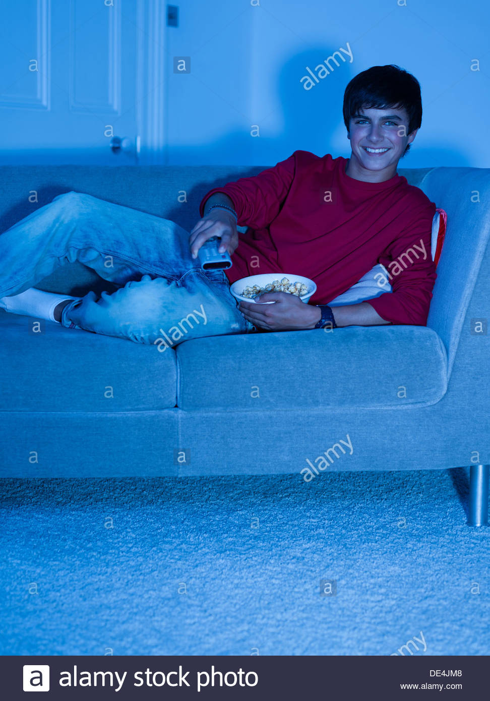 Smiling teenage boy laying on sofa with remote control - Stock Image