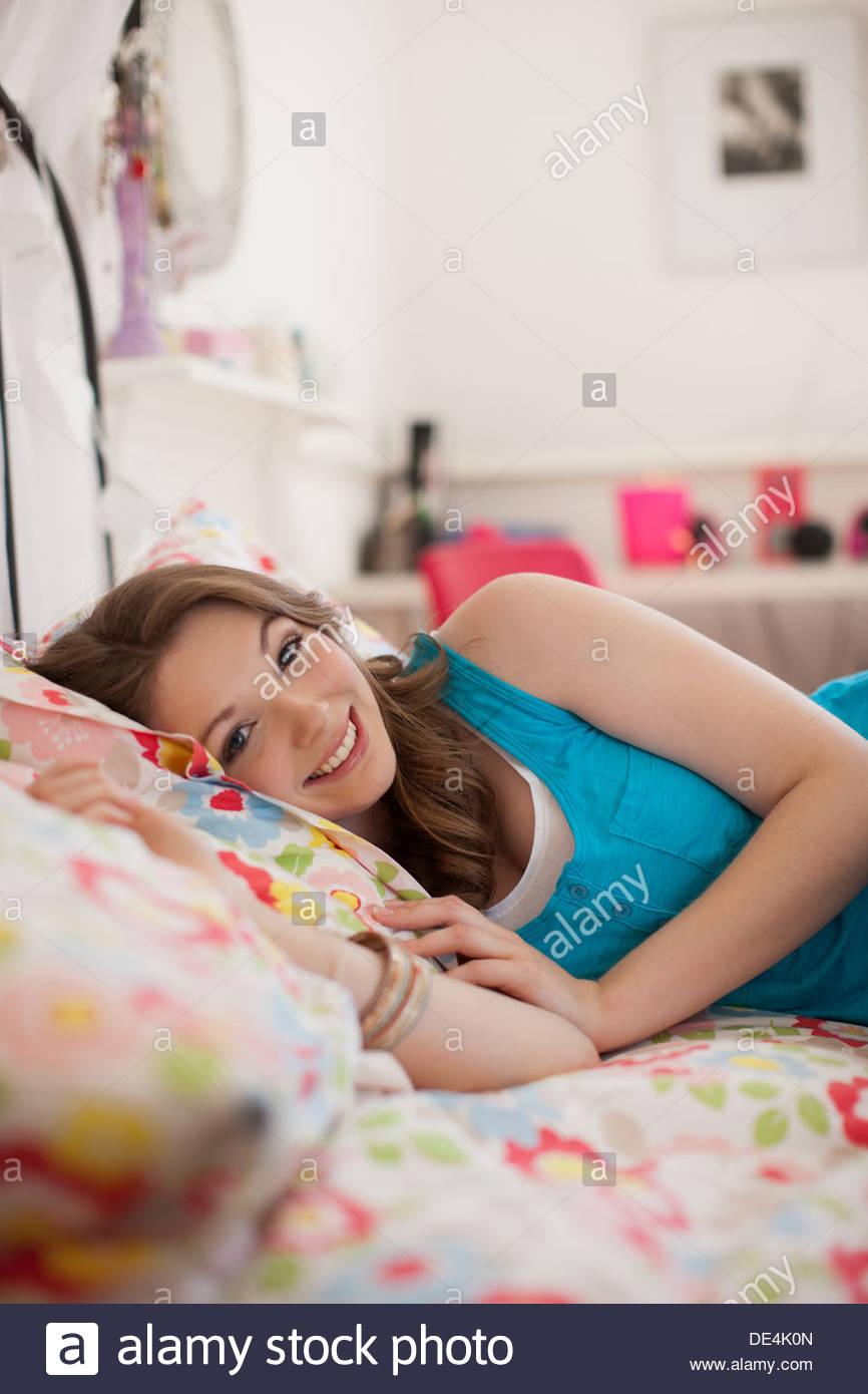 Smiling teenage girl lying on bed - Stock Image