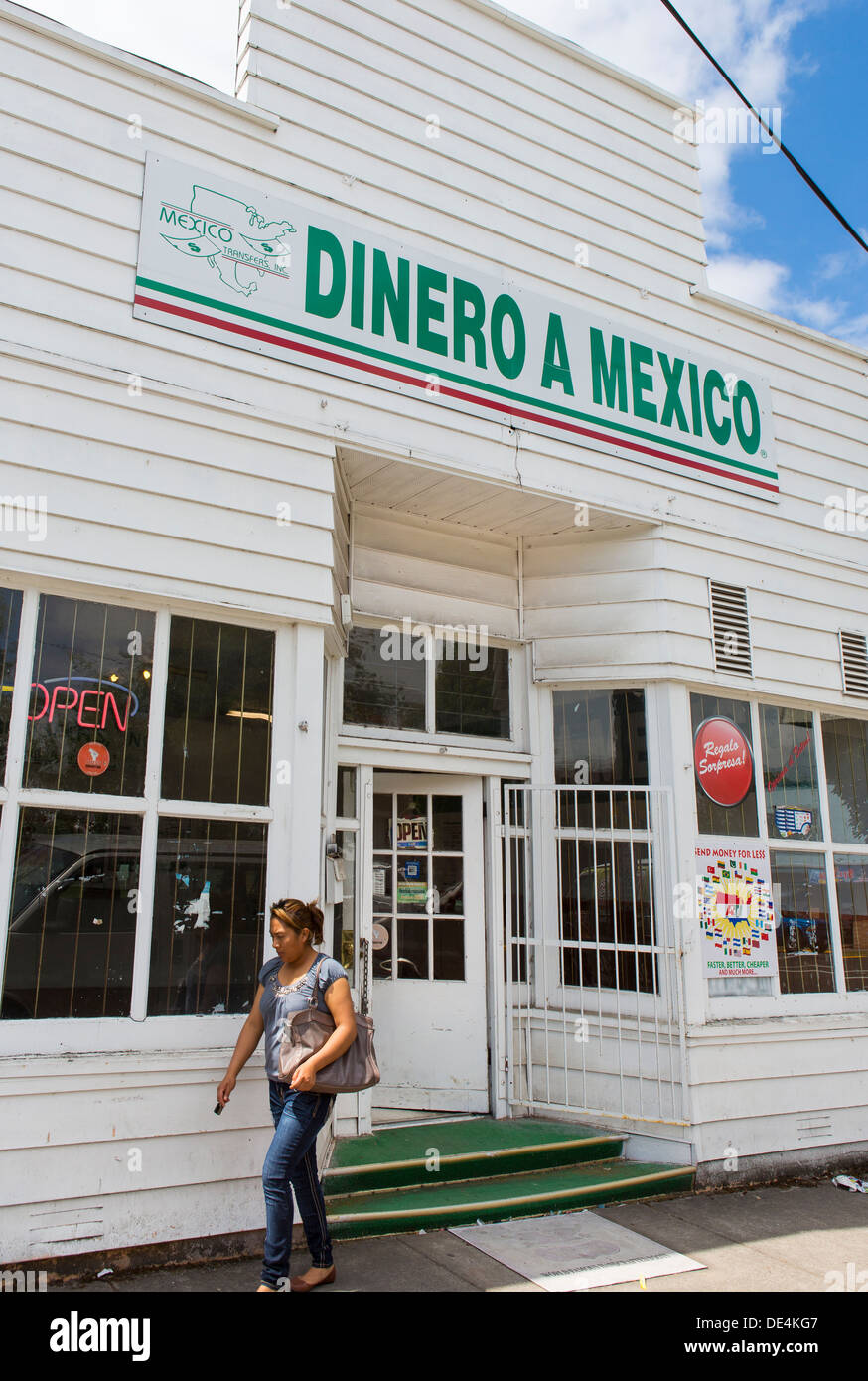 WOODBURN, OREGON, USA - Woman exits store with Dinero a Mexico sign that offers remittance service to Mexican immigrants. - Stock Image