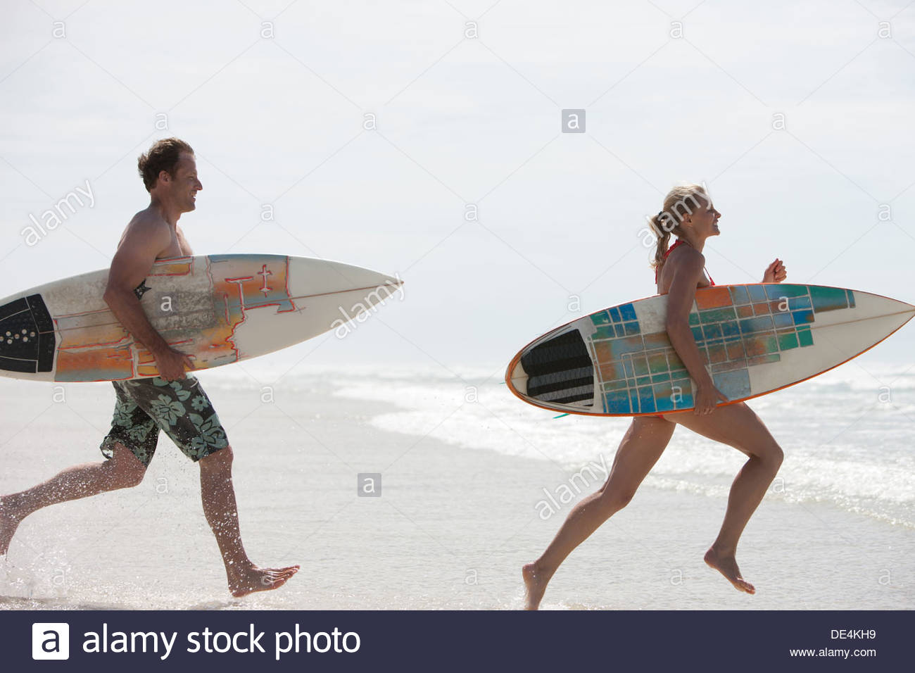 Couple with surfboards running on beach - Stock Image