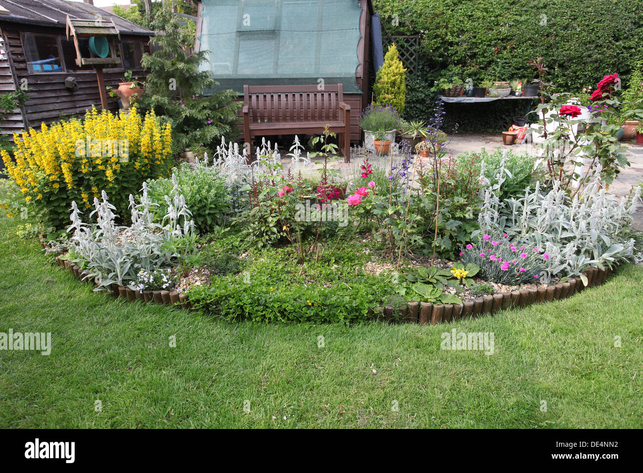 flower bed in half moon shape in english garden stock photo