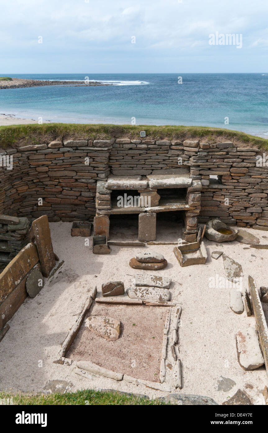 House 1 at Skara Brae Neolithic Village on Mainland Orkney with the Bay of Skaill in the background. Stock Photo