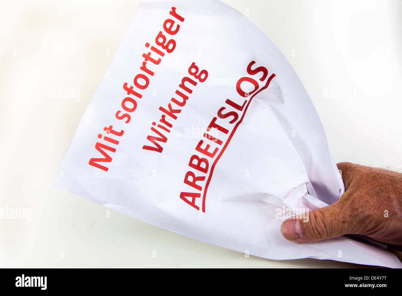Crumpled letter of termination to an employee, Mit sofortiger Wirkung arbeitslos, German for unemployed with immediate effect - Stock Image