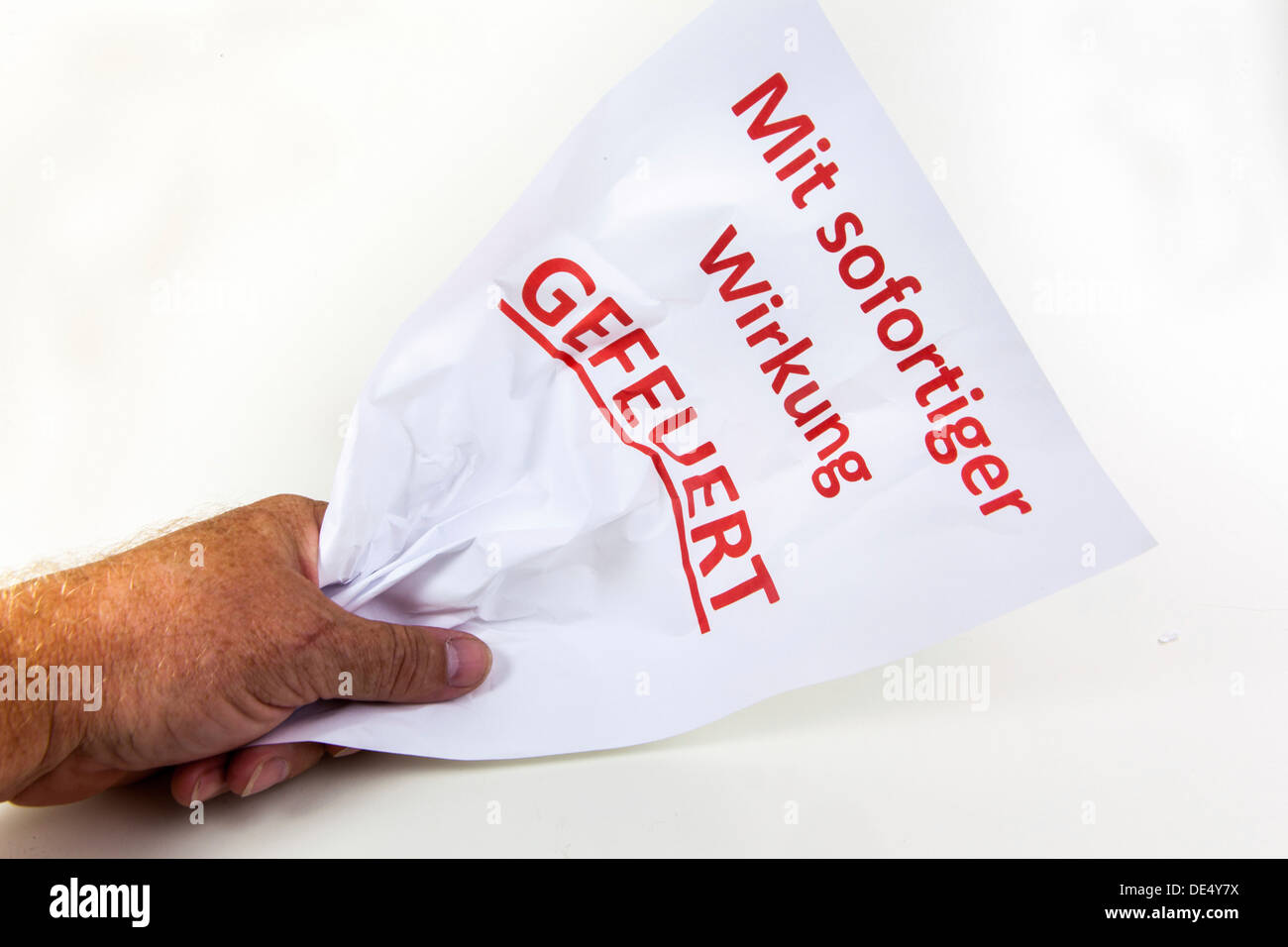 Crumpled letter of termination to an employee, Mit sofortiger Wirkung gefeuert, German for fired with immediate effect - Stock Image