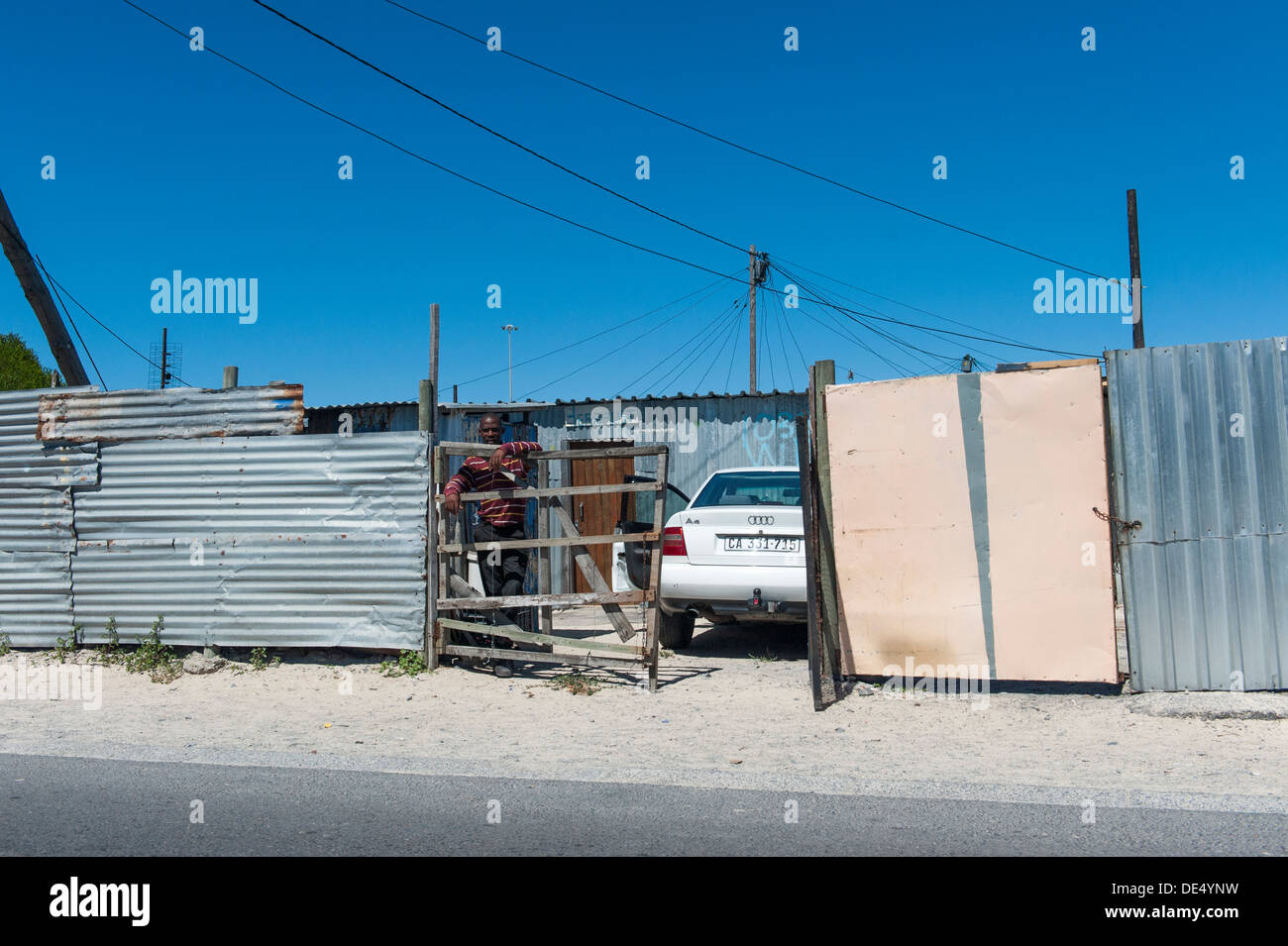 Car owner and parked car in front of a tin shack in Khayelitsha, Cape Town, South Africa Stock Photo