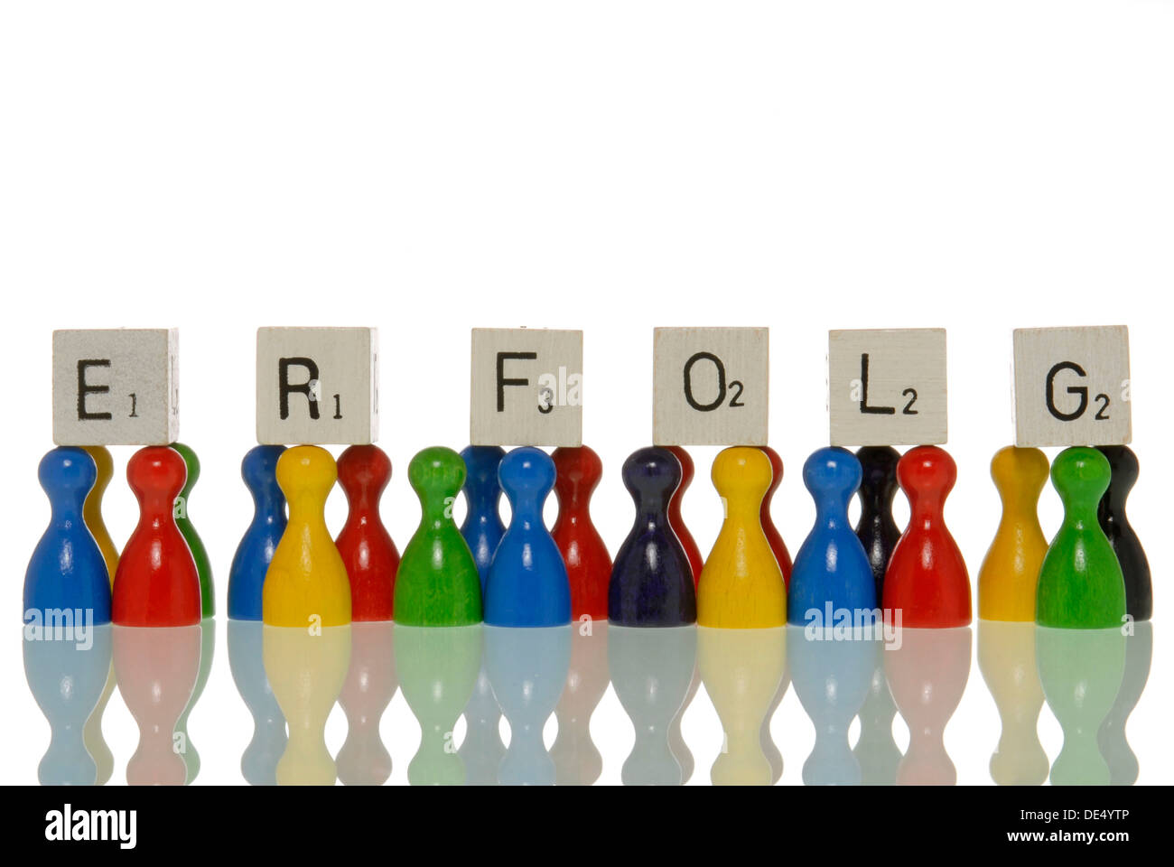 Game figures and letter tiles, spelling the word Erfolg, German for success - Stock Image