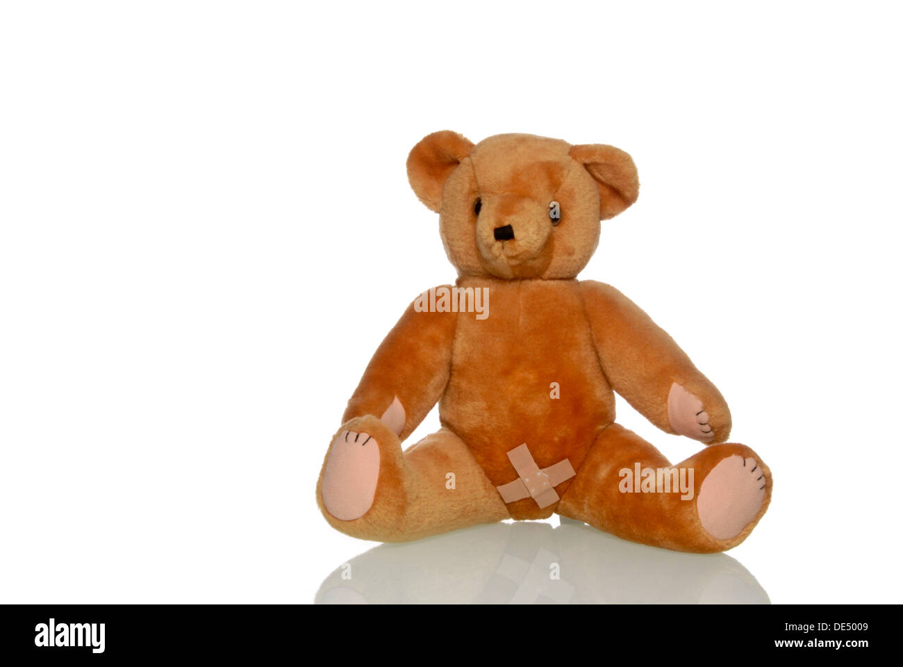 Sad teddy bear with a plaster in the genital area, symbolic image for abuse - Stock Image