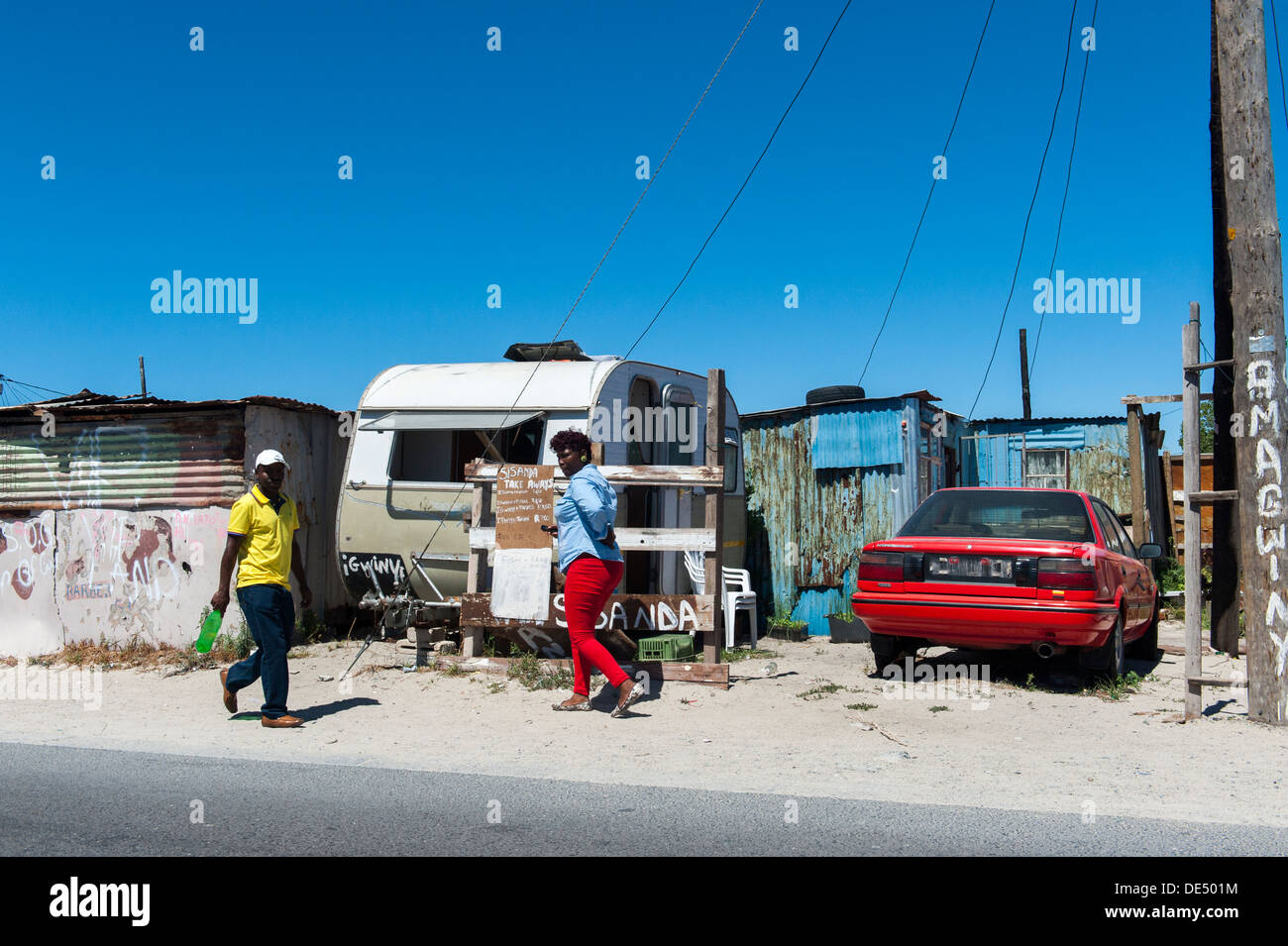 Man and woman walking along a street in Khayelitsha,  parked car and caravan in the background, Cape Town, South Africa - Stock Image