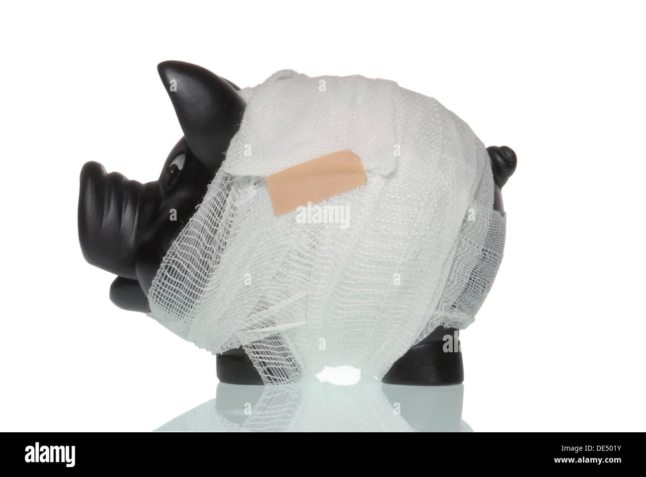 Bandaged piggy bank, symbolic image for sick banks - Stock Image