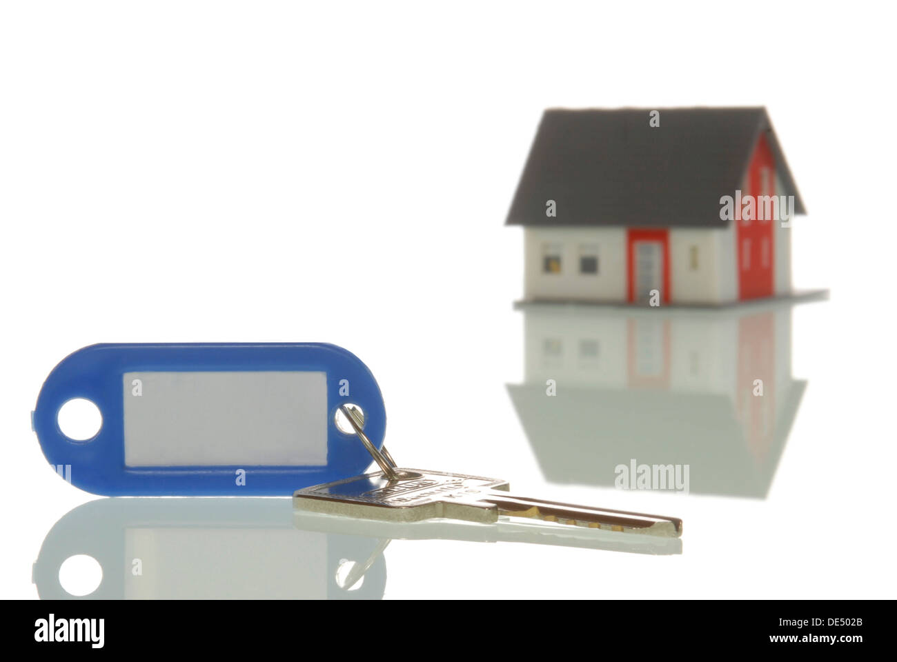 Key lying in front of a miniature house, symbolic image for property market - Stock Image