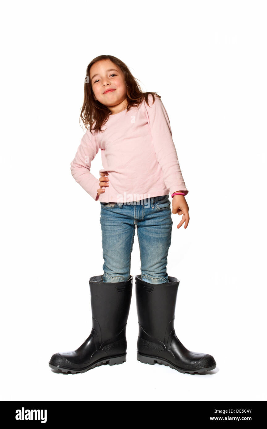 Seven-year-old girl wearing gumboots that are far too big - Stock Image
