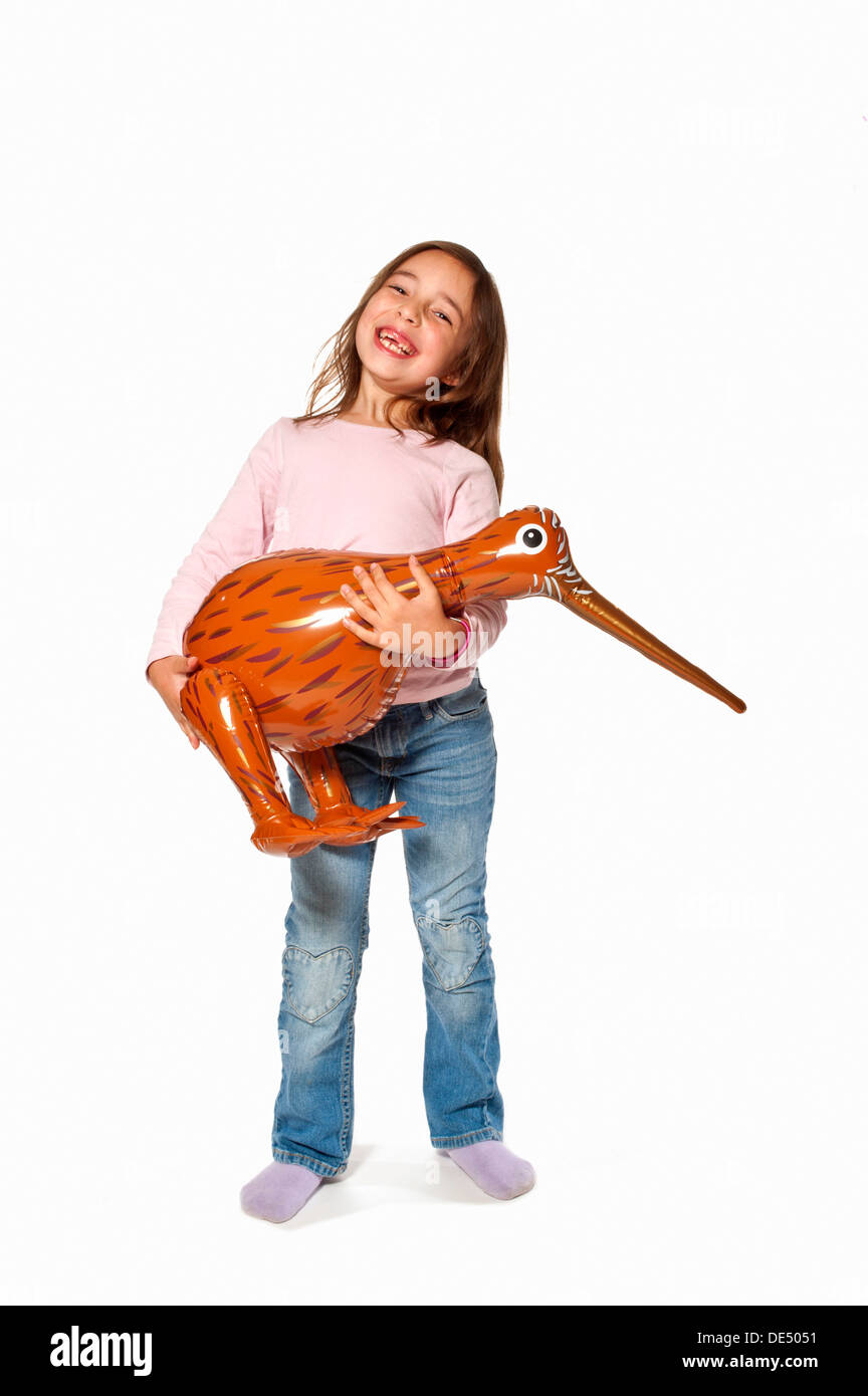 Seven-year-old girl holding an inflatable kiwi - Stock Image