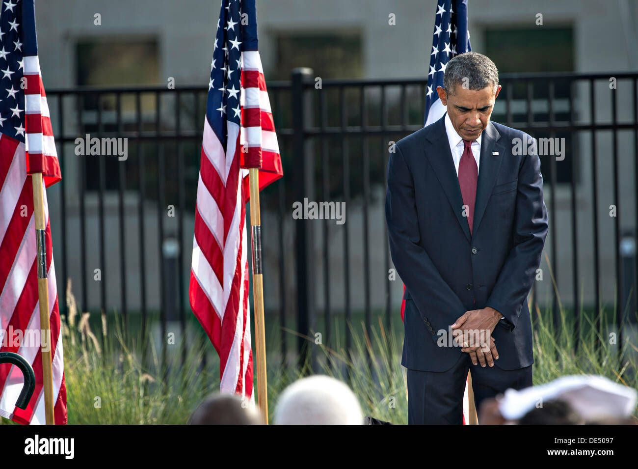 Arlington, Virginia, USA. 11th Sep, 2013. US President Barack Obama stands for a moment of silence during a remembrance ceremony to honor the victims of the 9/11 attacks on the Pentagon September 11, 2013 in Arlingotn, VA. Obama was joined Secretary of Defense Chuck Hagel and Chairman of the Joint Chiefs of Staff Martin Dempsey along with family members of those killed in the terrorist attack twelve years ago. Credit:  Planetpix/Alamy Live News - Stock Image