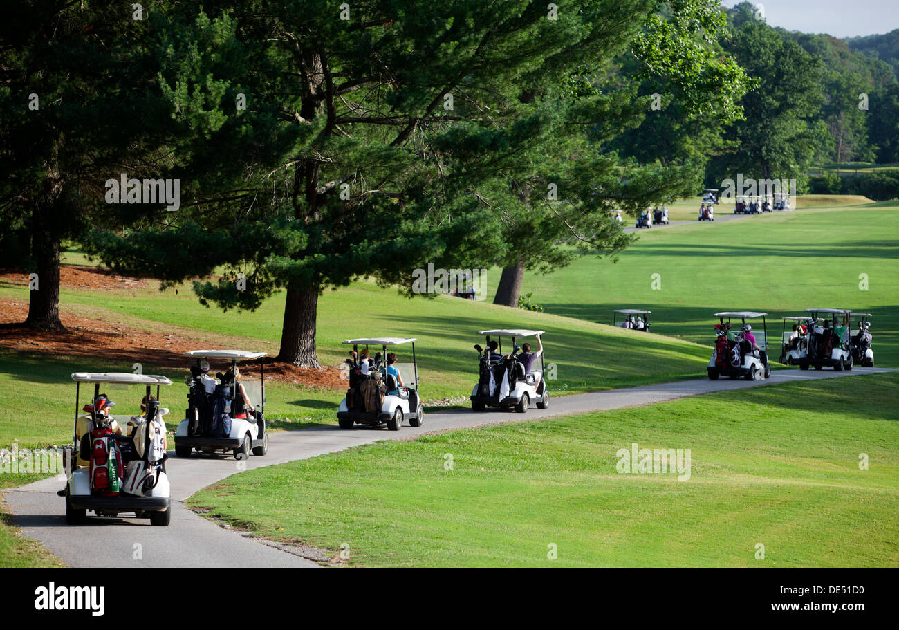 Golfers in their carts parade onto a golf course at the start of a tournament in Bella Vista, Arkansas. - Stock Image
