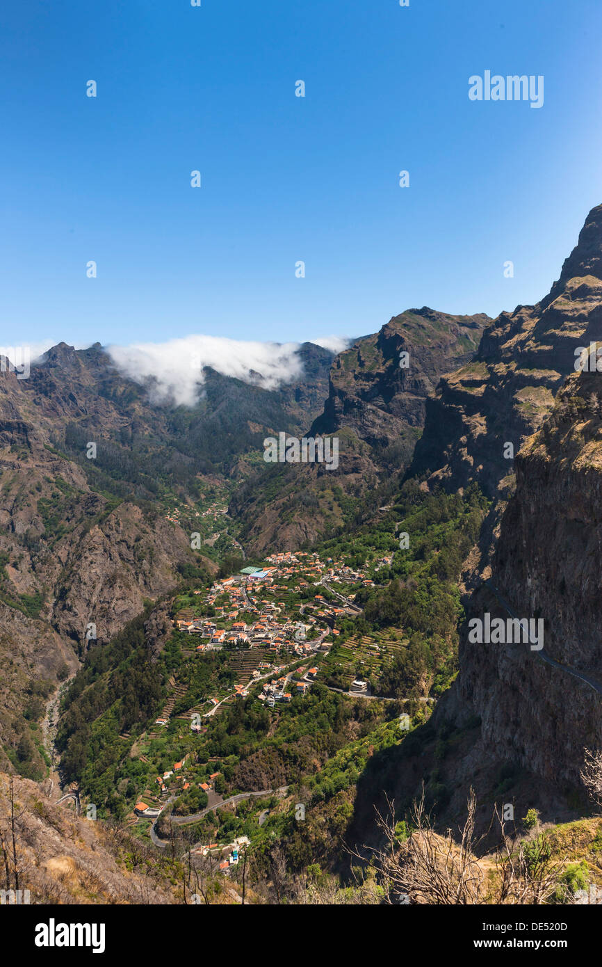 View of the village of Curral das Freiras seen from Pico dos Barcelos mountain, with its deep gorges, Curral das Freiras - Stock Image