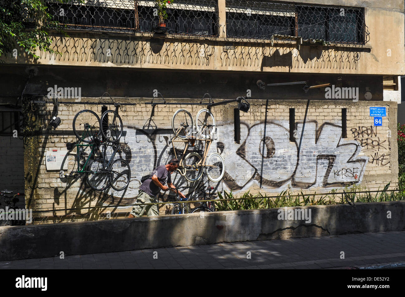 A bicycle shop owner in Rothschild Boulevard, Tel Aviv, Israel is removing a bike from a wall covered with graffiti - Stock Image