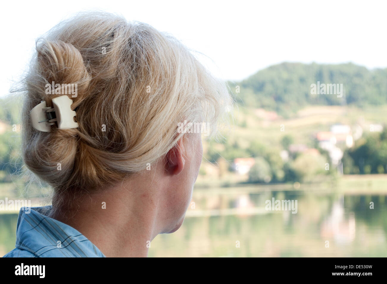 Middle aged woman looking at distant landscape - Stock Image