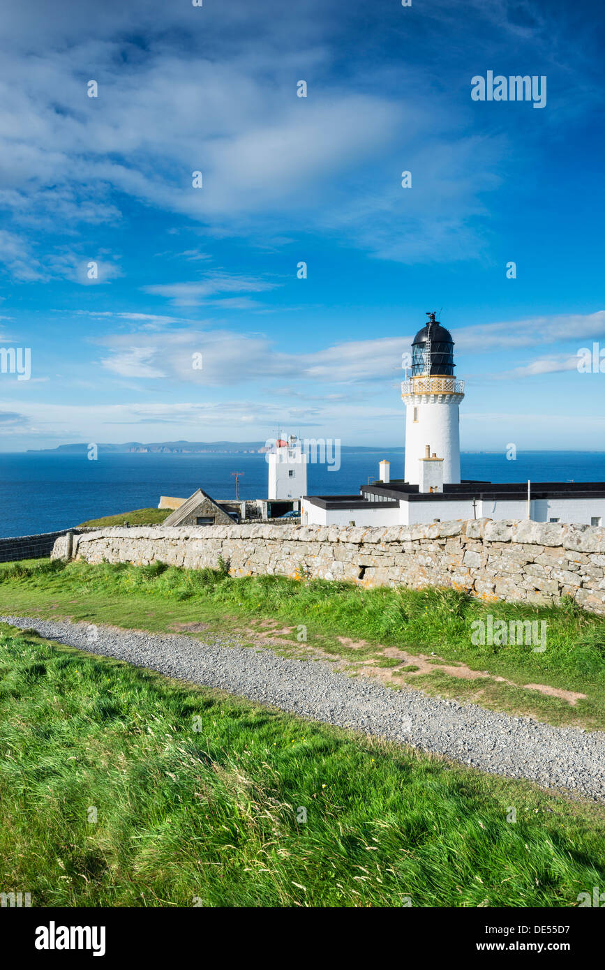 Dunnet Head lighthouse on the north coast of Scotland, Orkney Islands at back on the horizon, Caithness, Scotland - Stock Image