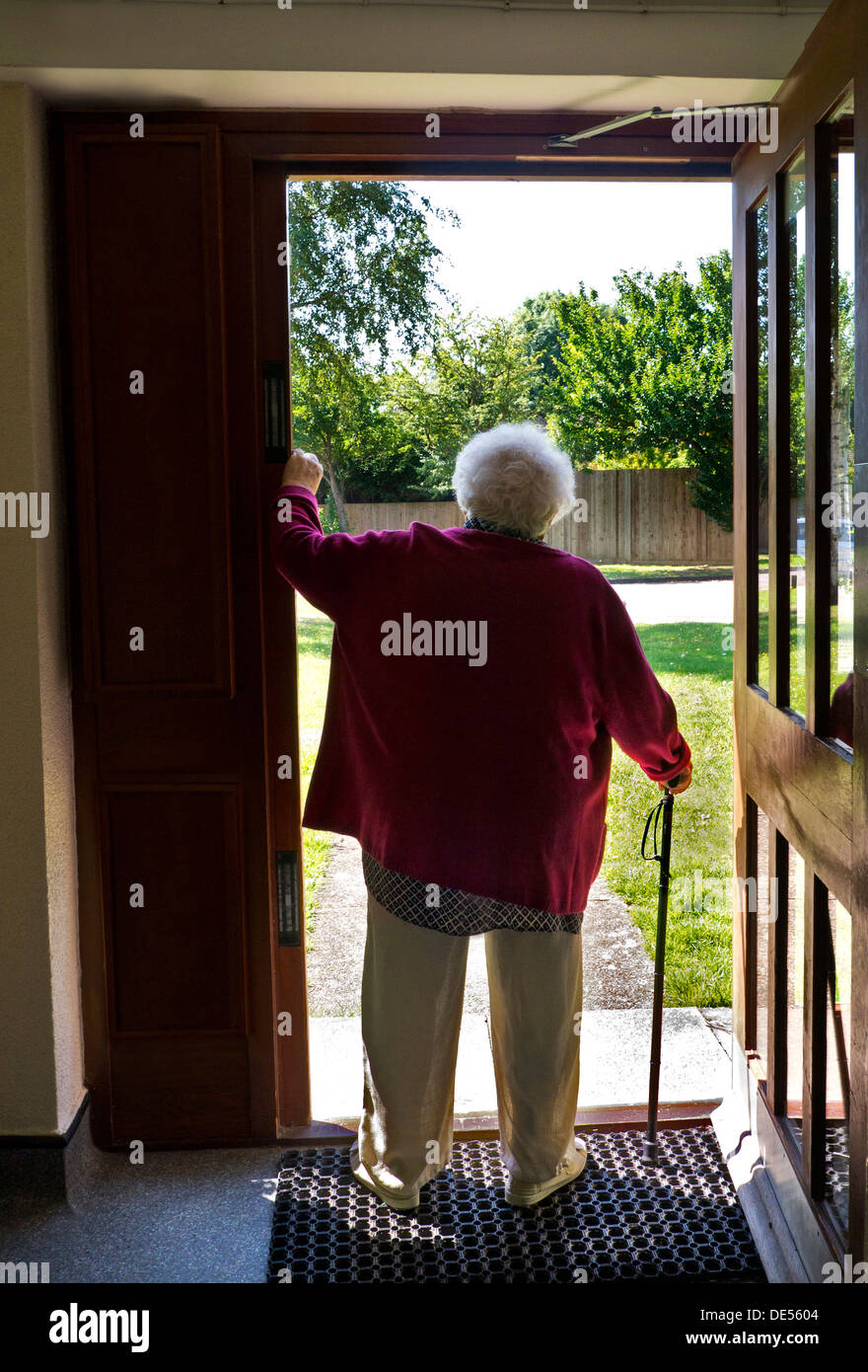 Pensive elderly senior old age lady standing alone with walking stick pauses at her open front door - Stock Image