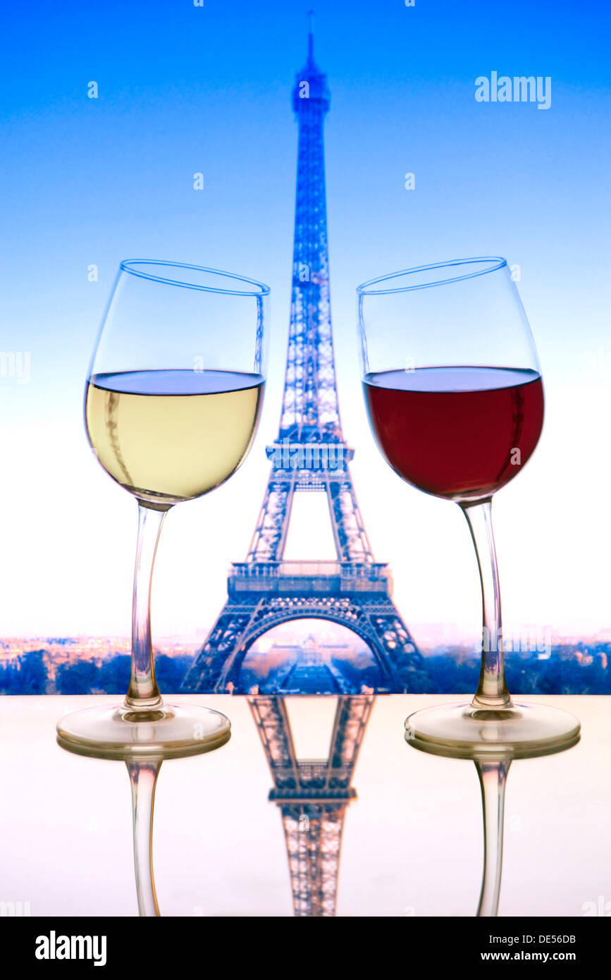 'Cheers' with red and white wine glasses leaning towards each other on cafe table with Eiffel Tower behind Paris France. - Stock Image