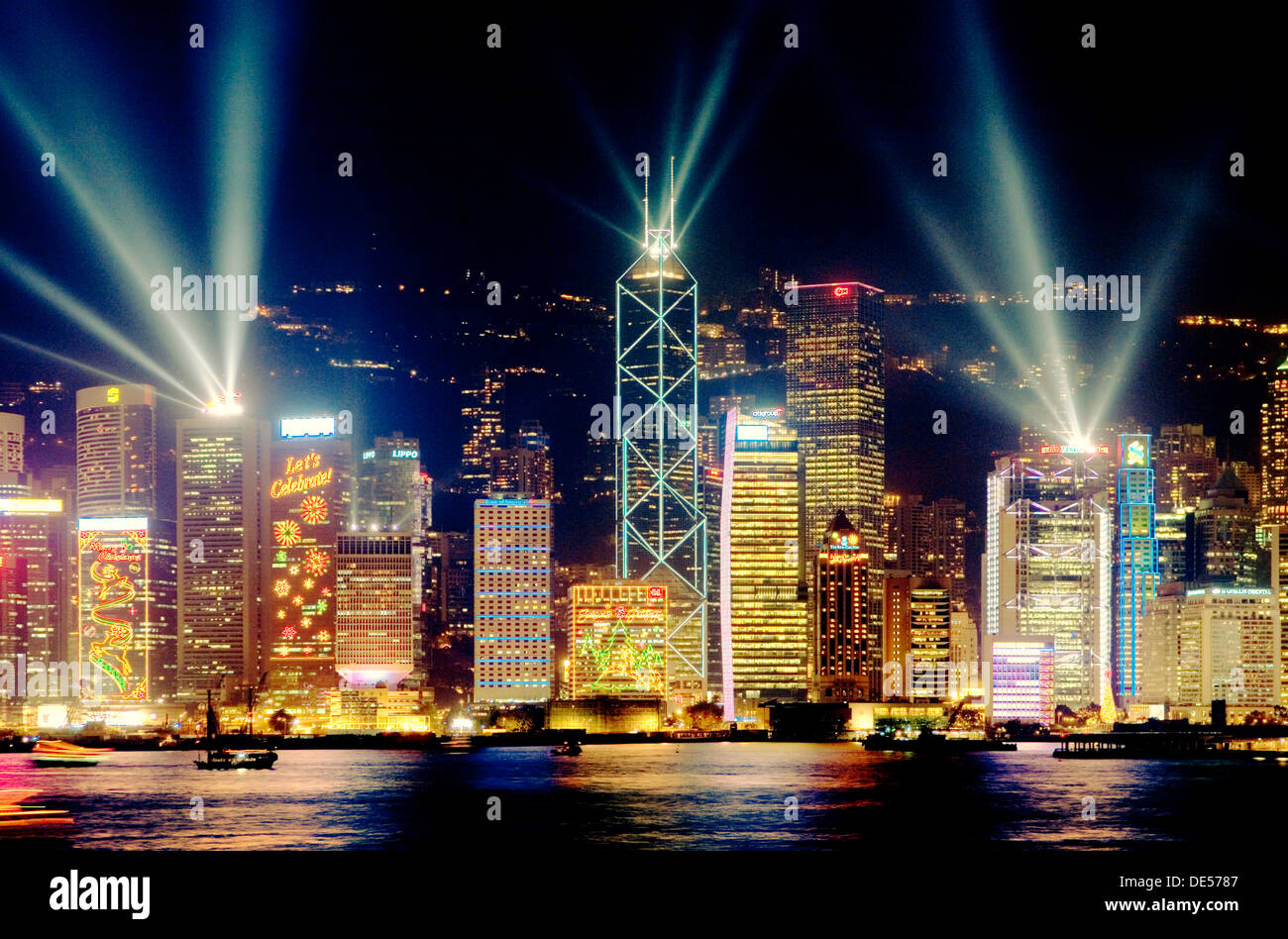 Hong Kong Island China city skyline of Central District at night with laser light show seen across Victoria Harbour from Kowloon - Stock Image