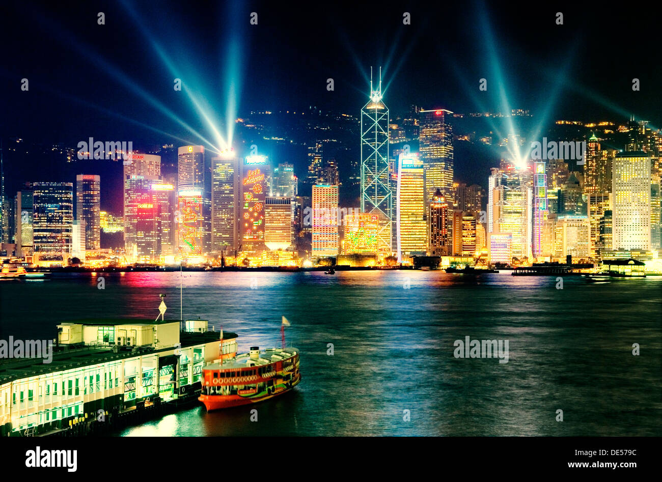 Hong Kong Island China city skyline with night laser light show seen across Victoria Harbour from Kowloon Star Ferry terminal - Stock Image