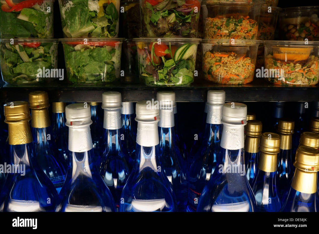 Prepared salads and bottled water in a cafe display case - Stock Image