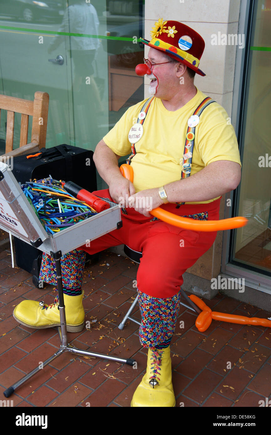 Jolly middle-aged male clown making balloon hats, Vancouver, British Columbia, Canada Stock Photo