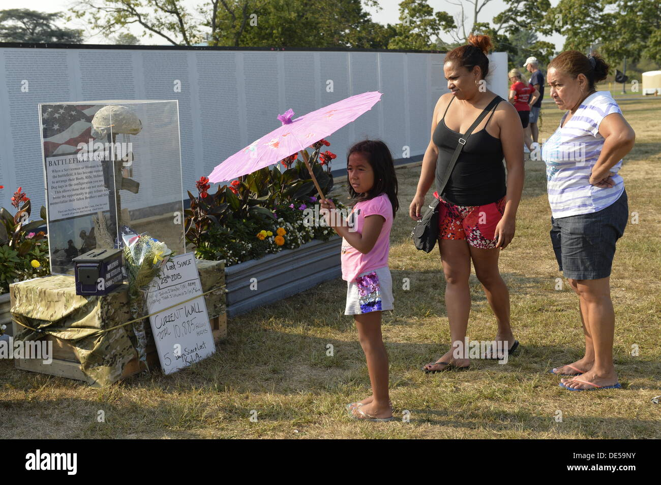 East Meadow, New York, U.S. 11th September 2013. A young girl and family look at the Battlefield Cross display at the Global War on Terror 'Wall of Remembrance' a traveling memorial on display in New York for the first time, at Eisenhower Park on the 12th Anniversary of the terrorist attacks of 9/11. The unique 94 feet long by 6 feet high wall has, on one side, almost 11,000 names of those lost on September 11, 2001, along with heroes and veterans who lost their lives defending freedom of Americans over past 30 years.  © Ann E Parry/Alamy Live News - Stock Image